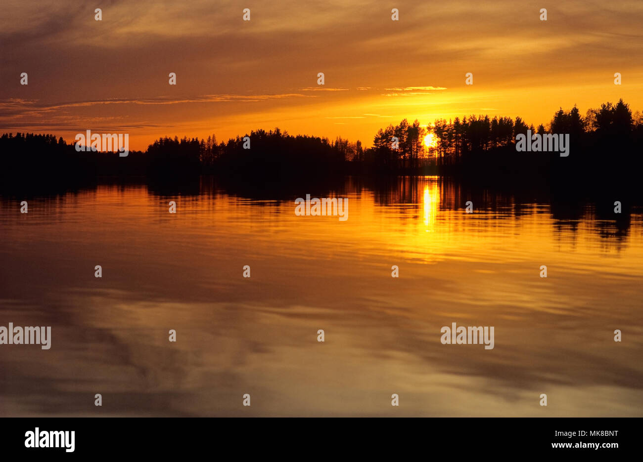Sunset with intense colors over lake in Finland. - Stock Image