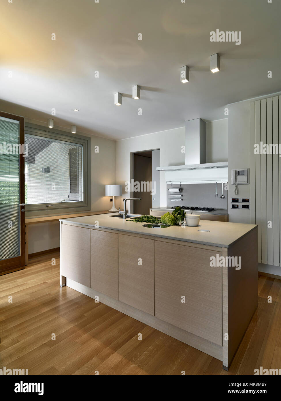 interiors shots of a modern kitchen with kitchen island with wooden floor - Stock Image