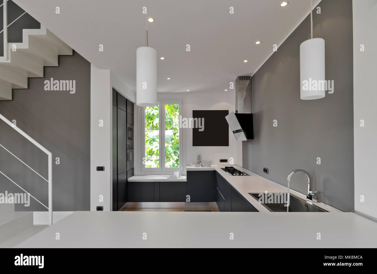 interiors shots of a modern kitchen in the foreground the integrated sink with his faucet - Stock Image