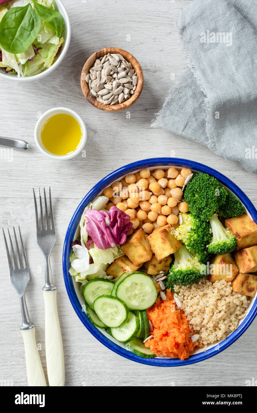 Colorful buddha bowl, healthy vegetarian salad. Buddha bowl with sweet potato, quinoa, chickpeas, broccoli, baked tofu, cucumber and green salad leaf. Stock Photo