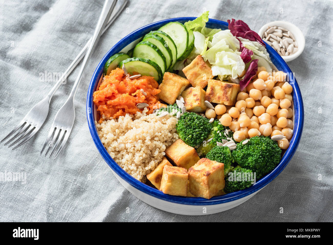 Nourishing buddha bowl with tofu, quinoa and vegetables. Healthy eating, healthy lifestyle, vegan food, vegetarian diet, modern lifestyle concept. Col - Stock Image