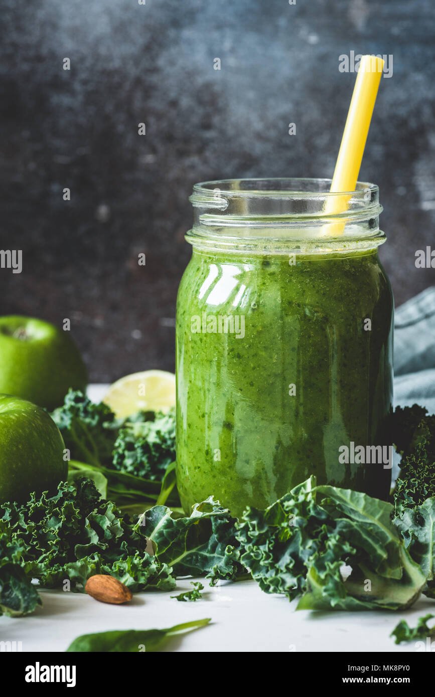 Green detox smoothie in a mug. Concept of vegetarian, vegan diet, detox, healthy lifestyle and healthy eating. Vertical, toned image. - Stock Image