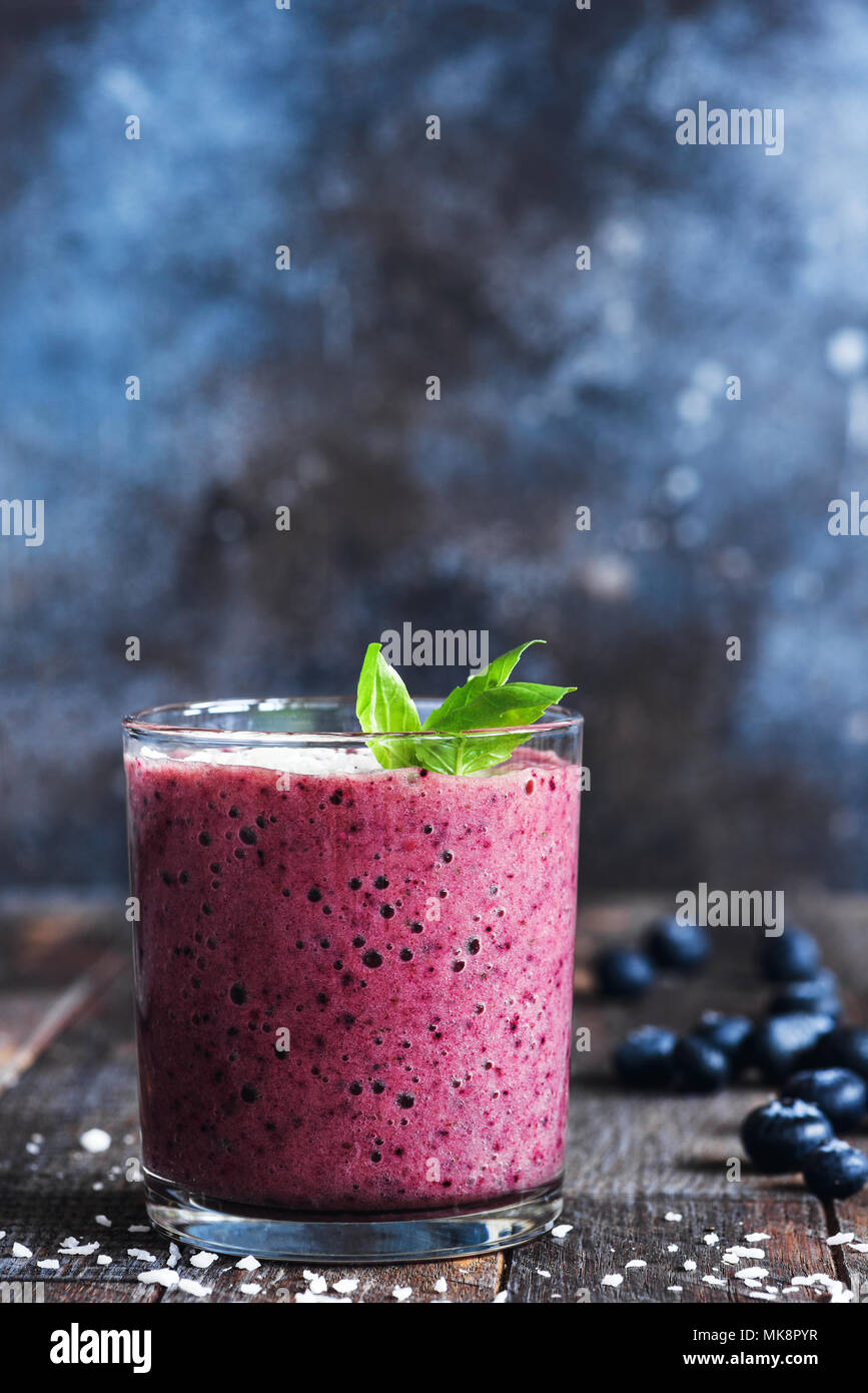 Blueberry smoothie decorated with basil leaf. Glass of healthy blueberry or berry smoothie on dark table, selective focus. Vegan or vegetarian nutriti - Stock Image