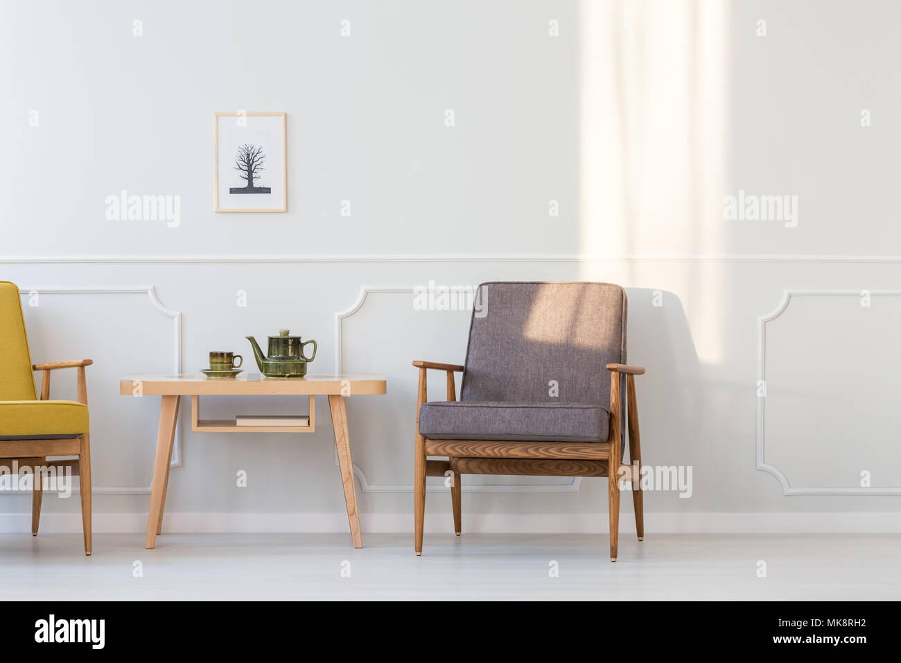Grey wooden armchair next to table in minimal living room interior ...