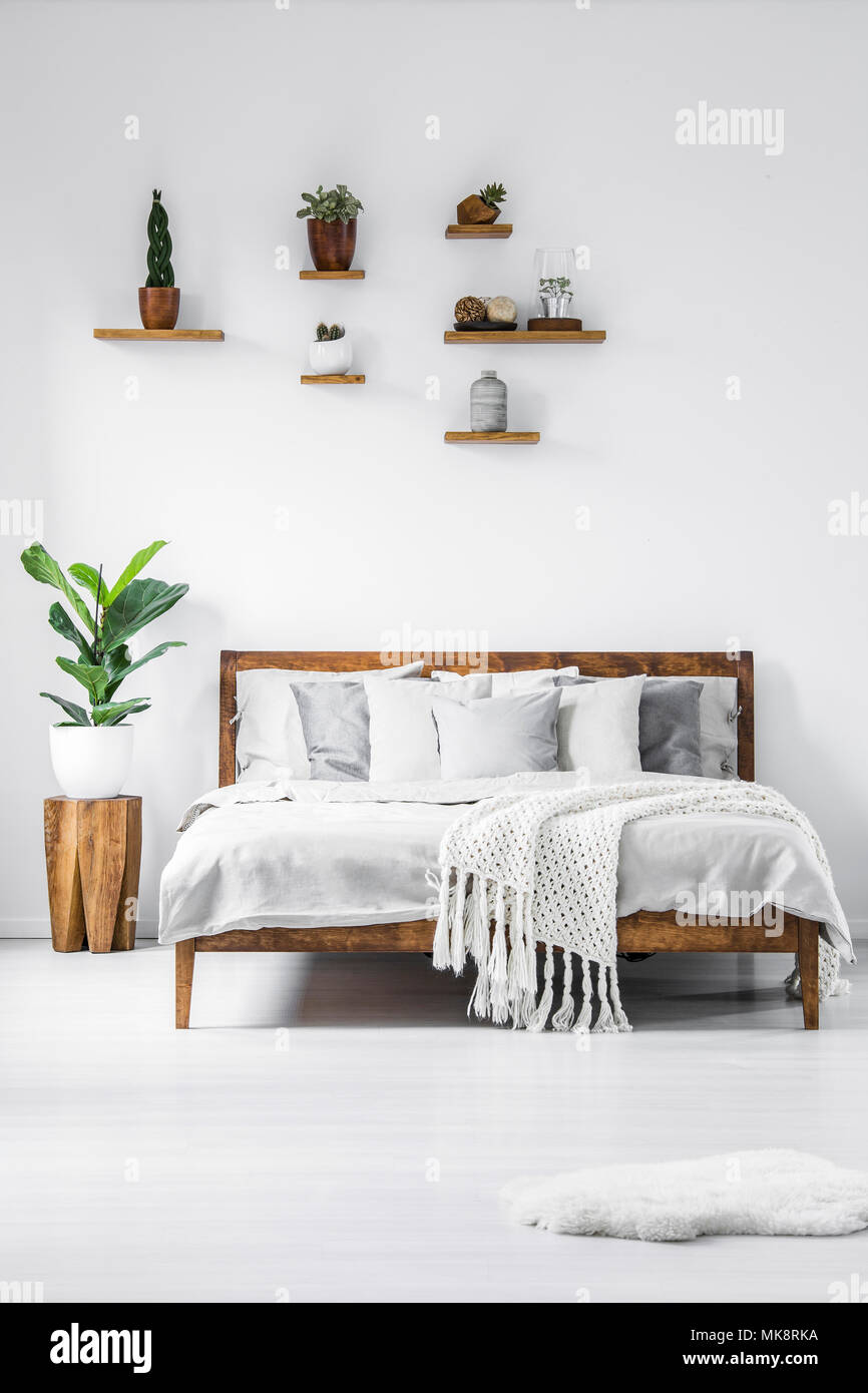Plant on wooden stool next to bed in simple white bedroom ...