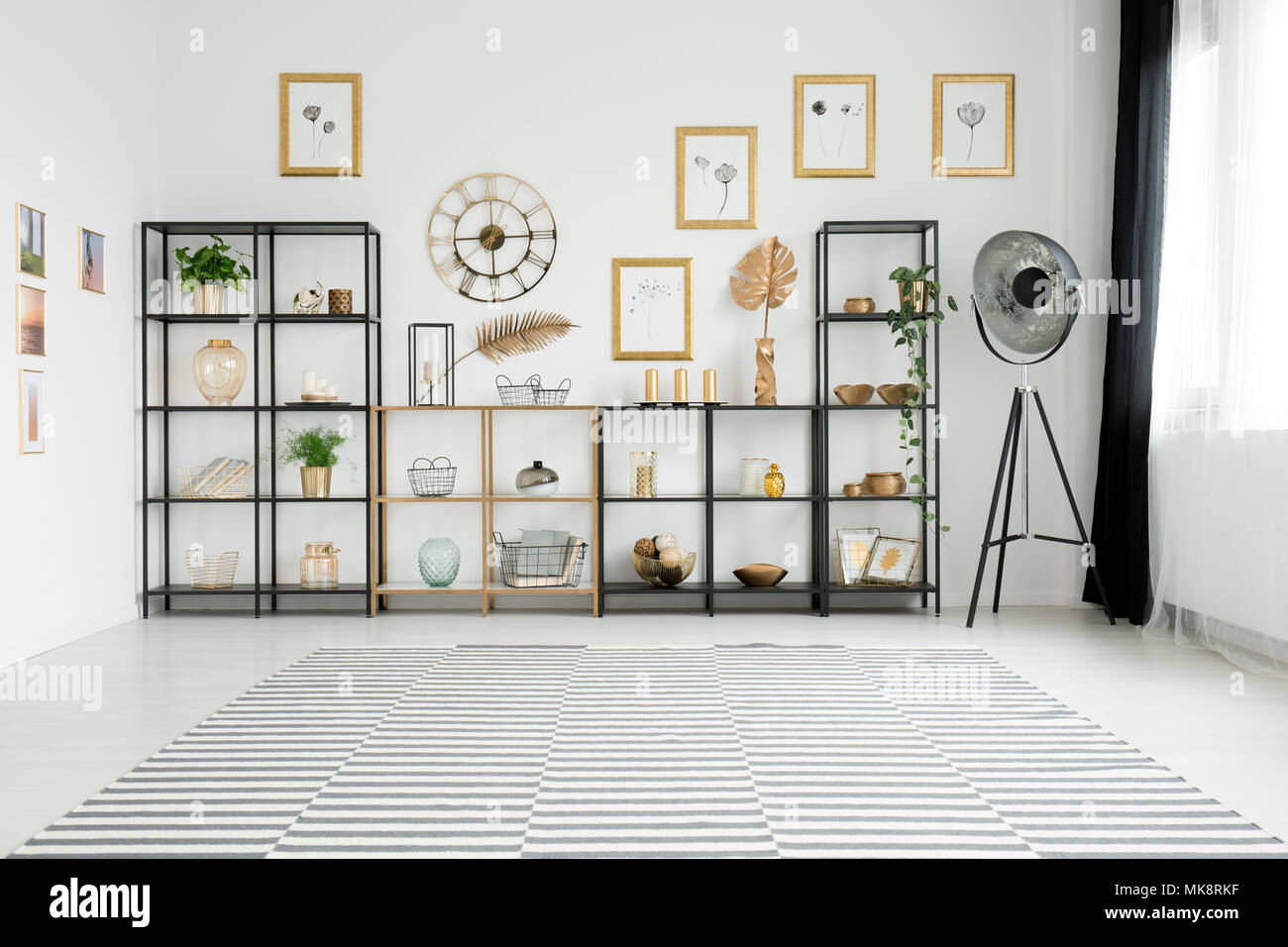 Spacious living room interior with lots of decorations on gold and black racks standing against a white wall with pictures gallery Stock Photo