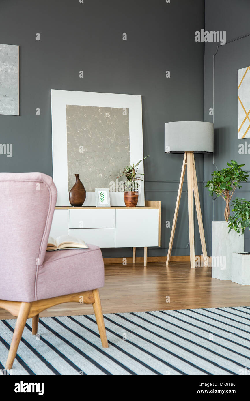 Pink Armchair On Striped Rug In Grey Living Room Interior With