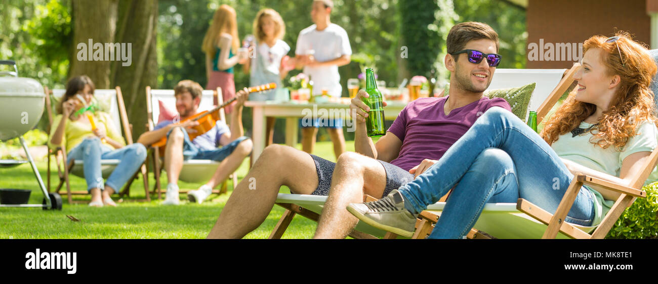 Young couple talking during a grill party in the countryside Stock Photo