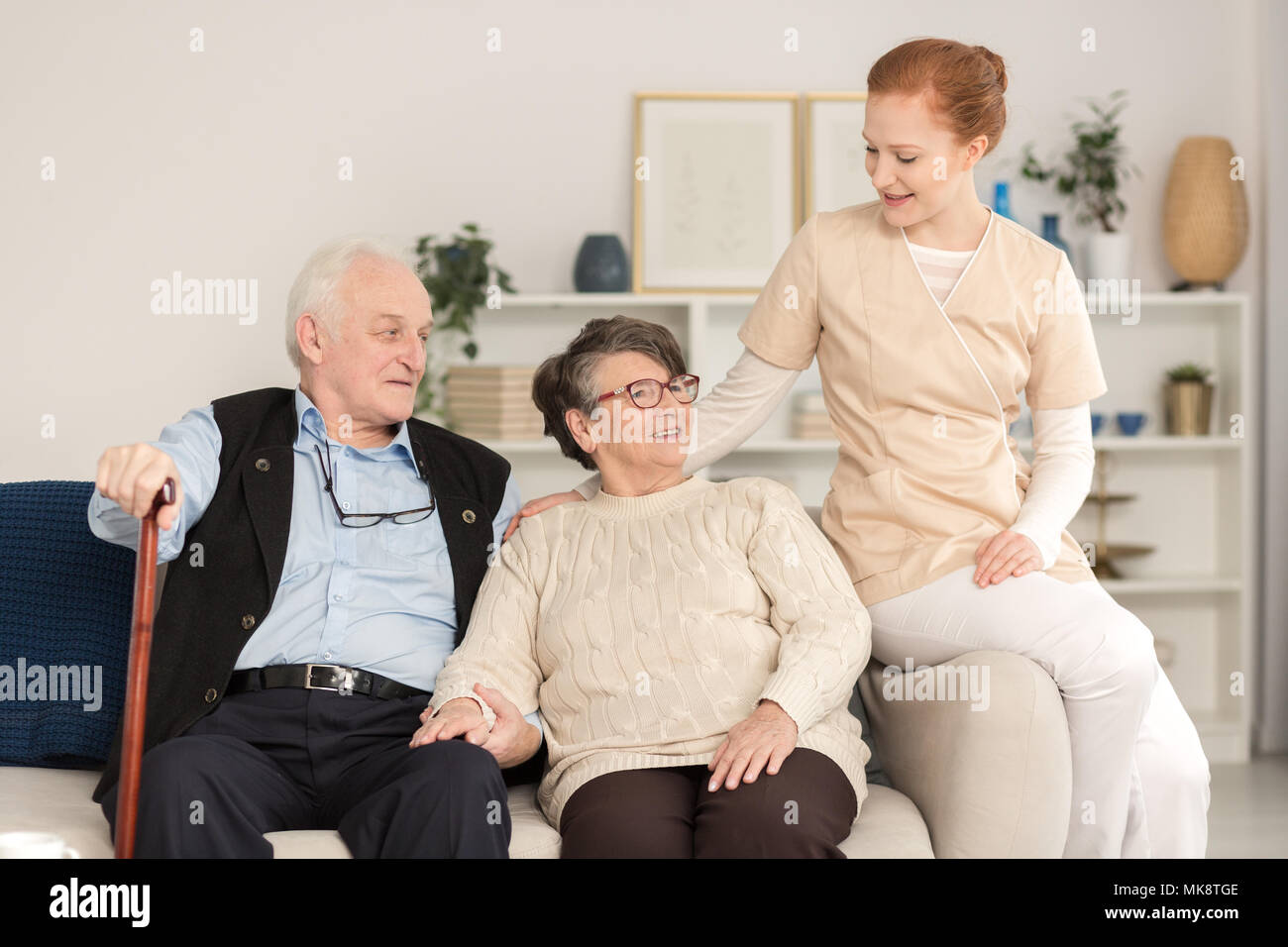 Professional assistant supporting and consoling a worried senior married couple in a living room of a day care center - Stock Image