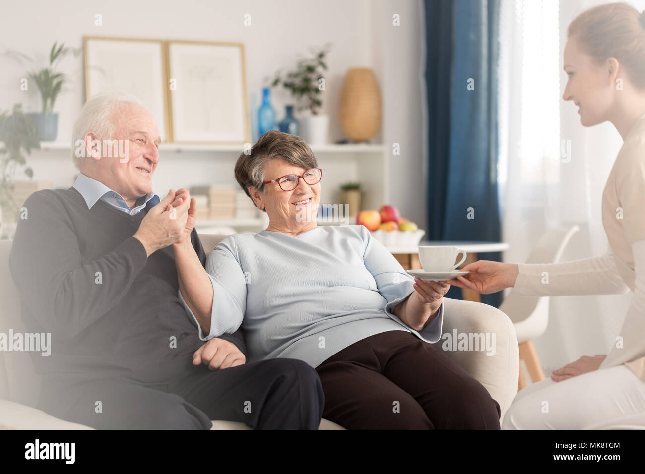 Young at heart emotional senior couple holding hands while sitting on settee and being served by a caregiver a cup of tea in a sunny living room at ho - Stock Image