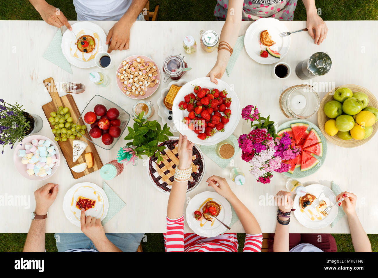 Multicultural group having a meal, sharing food in the garden outside on a sunny day - Stock Image
