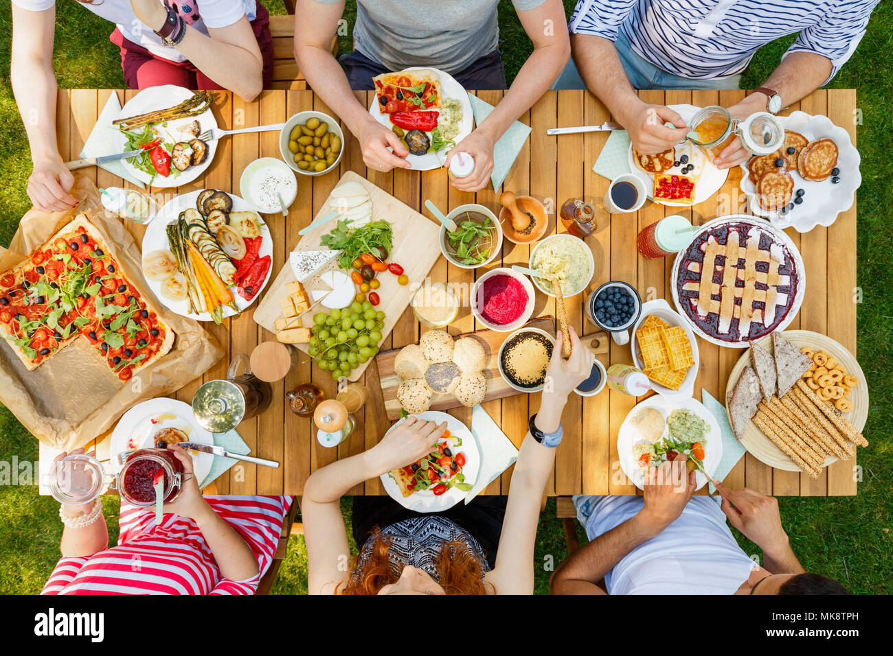 Friends eating healthy food like vegan pizza and fruit outdoors in the park on a rustic table - Stock Image