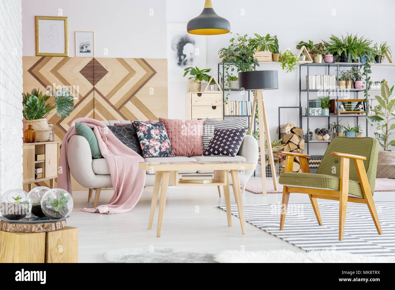 Botanical living room interior with comfy couch and pillows, armchair, wooden coffee table and wall - Stock Image