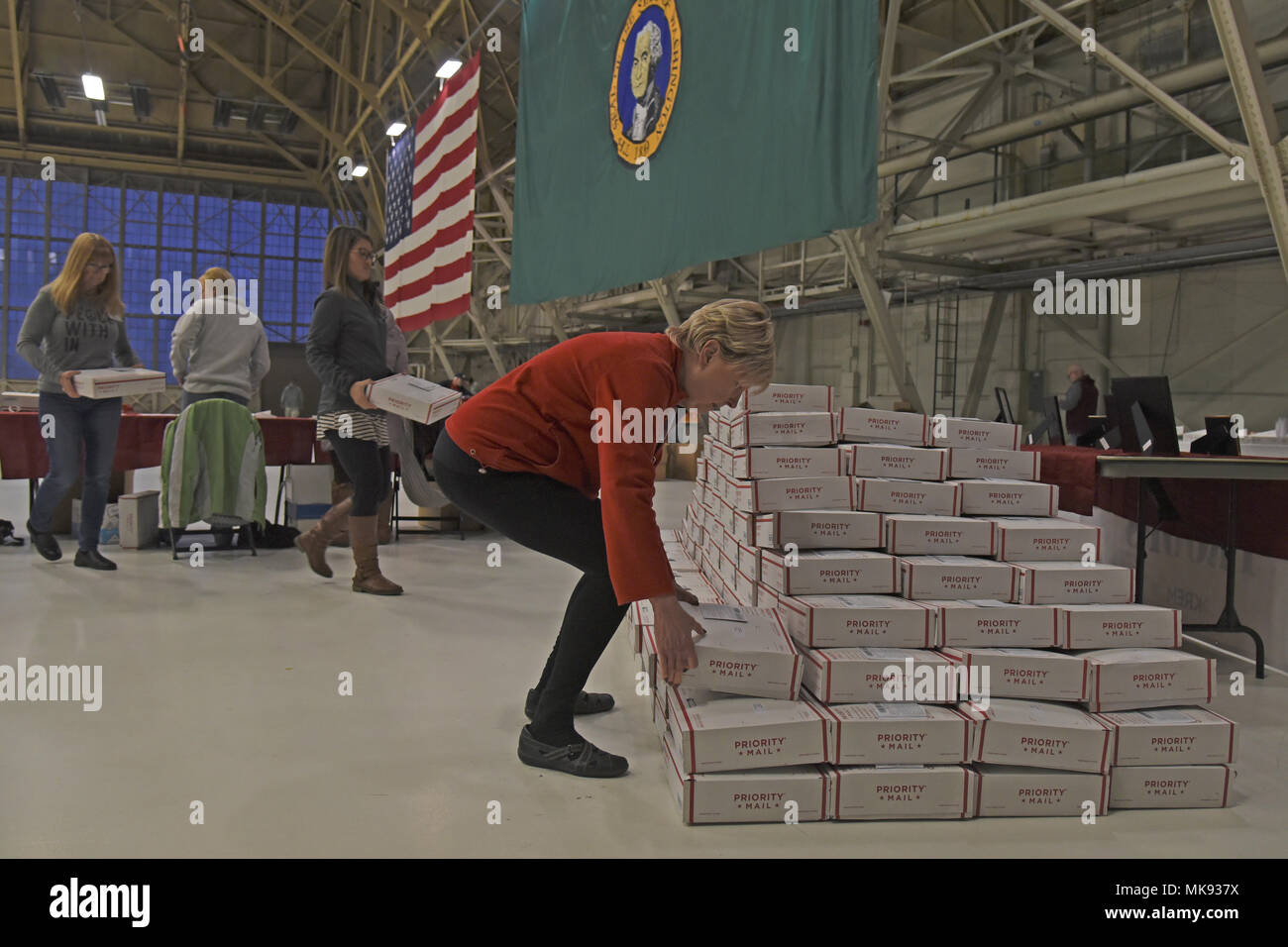 Team Fairchild volunteers stack completed Treats 2 Troops care packages Nov. 29, 2017, at Fairchild Air Force Base, Washington. KREM 2 News partnered with Team Fairchild for the seventh year in a row to fill care packages with small treats and gifts such as sunflower seeds, chewing gum, hand sanitizer, homemade knit hats and holiday cards made by local schools. (U.S. Air Force photo/Senior Airman Mackenzie Richardson) - Stock Image