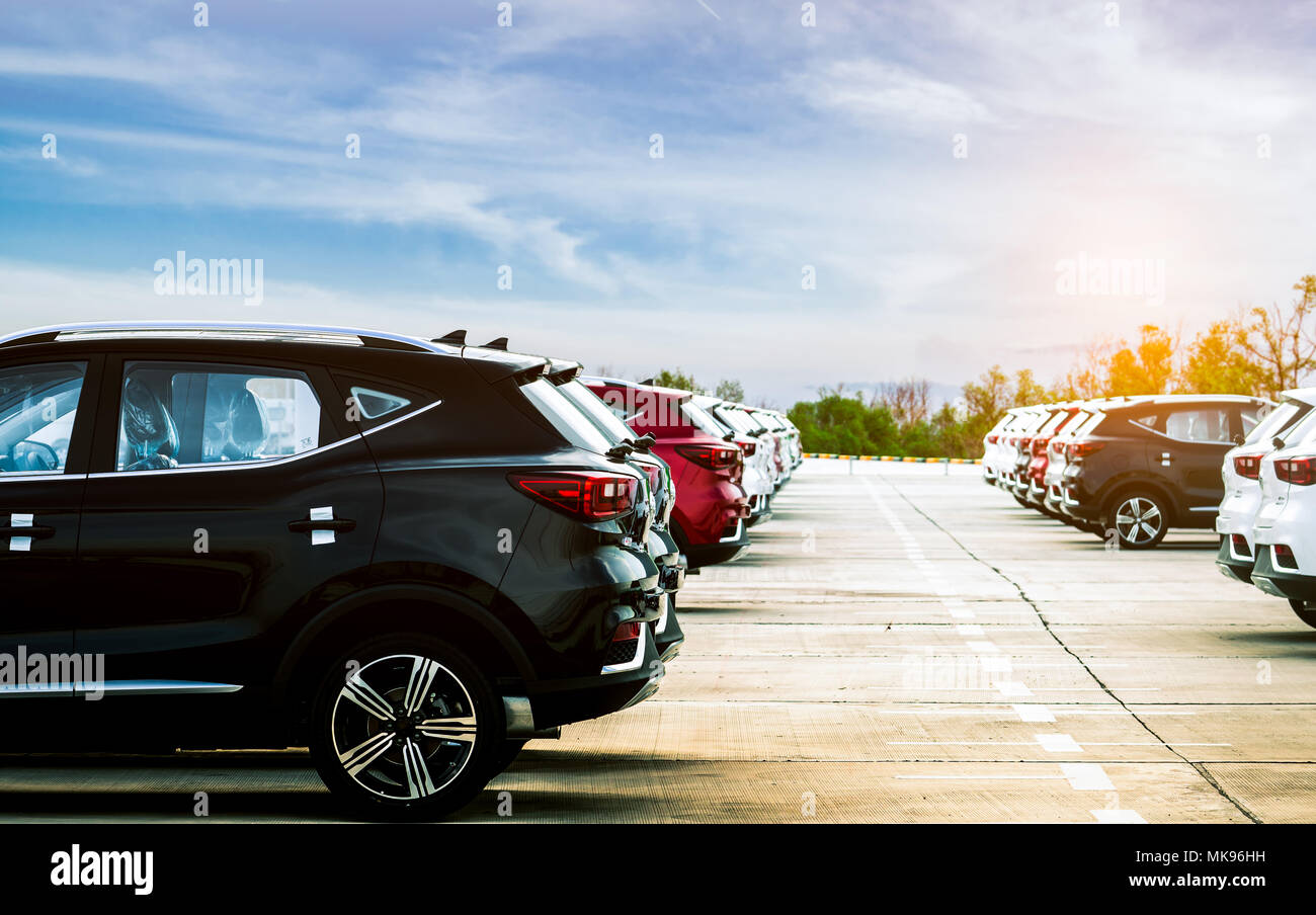 Luxury black, white and red new suv car parked on concrete parking area at factory with blue sky and clouds. Car stock for sale. Car factory parking l - Stock Image