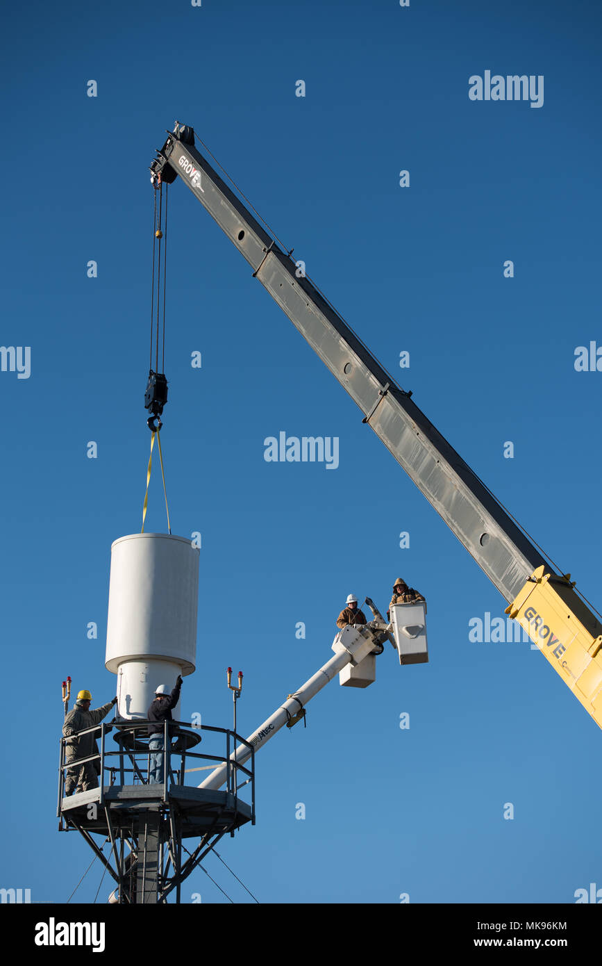 Airmen and contractors guide Offutt Air Force Base's (AFB) legacy Tactical Air Navigation System (TACAN) as a crane operator hoists the system off its tower at Offutt AFB, Nebraska, Nov. 29, 2017. The TACAN is a beacon which communicates bearing and distance information to incoming aircraft within 200 nautical miles. An Air Force-wide modernization project mandated the TACANs replacement. (U.S. Air Force photo by Senior Airman Jacob Skovo) - Stock Image