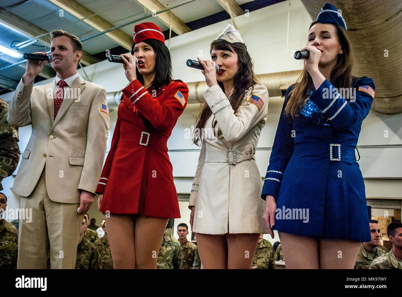 Brandon Riddle, Zoe Friedman, Amanda Downey, and Erin Long, members of the New York City based USO Show Troupe, sing the National Anthem prior to the beginning of the lottery portion of the 20th annual Randy Oler Memorial Operation Toy Drop, Dec. 1, 2017. Operation Toy Drop is the world's largest combined airborne operation with nine partner nation paratroopers participating and allows Soldiers the opportunity to train on their military occupational specialty, maintain their airborne readiness, and give back to the local community. (U.S. Army photo by Staff Sgt. Timothy R. Koster) - Stock Image