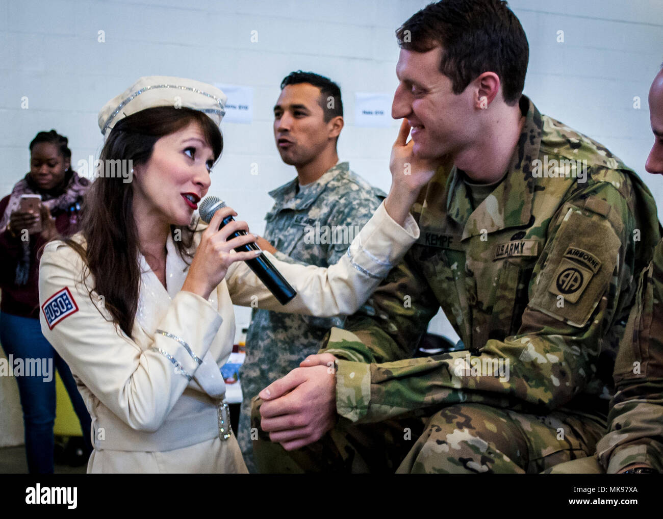 Amanda Downey, a member of the New York City based USO Show Troupe, sings a song to 1st Lt. Alexander Kempf, 32nd Engineer Company, 2nd Brigade, 82nd Airborne Division, during the lottery portion of the 20th Annual Randy Oler Memorial Operation Toy Drop, Dec. 1, 2017. Operation Toy Drop, hosted by the U.S. Army Civil Affairs & Psychological Operations Command (Airborne) and is the largest combined airborne operation conducted worldwide. The event and allows Soldiers the opportunity to train on their military occupational specialty, maintain their airborne readiness, and give back to the lo - Stock Image