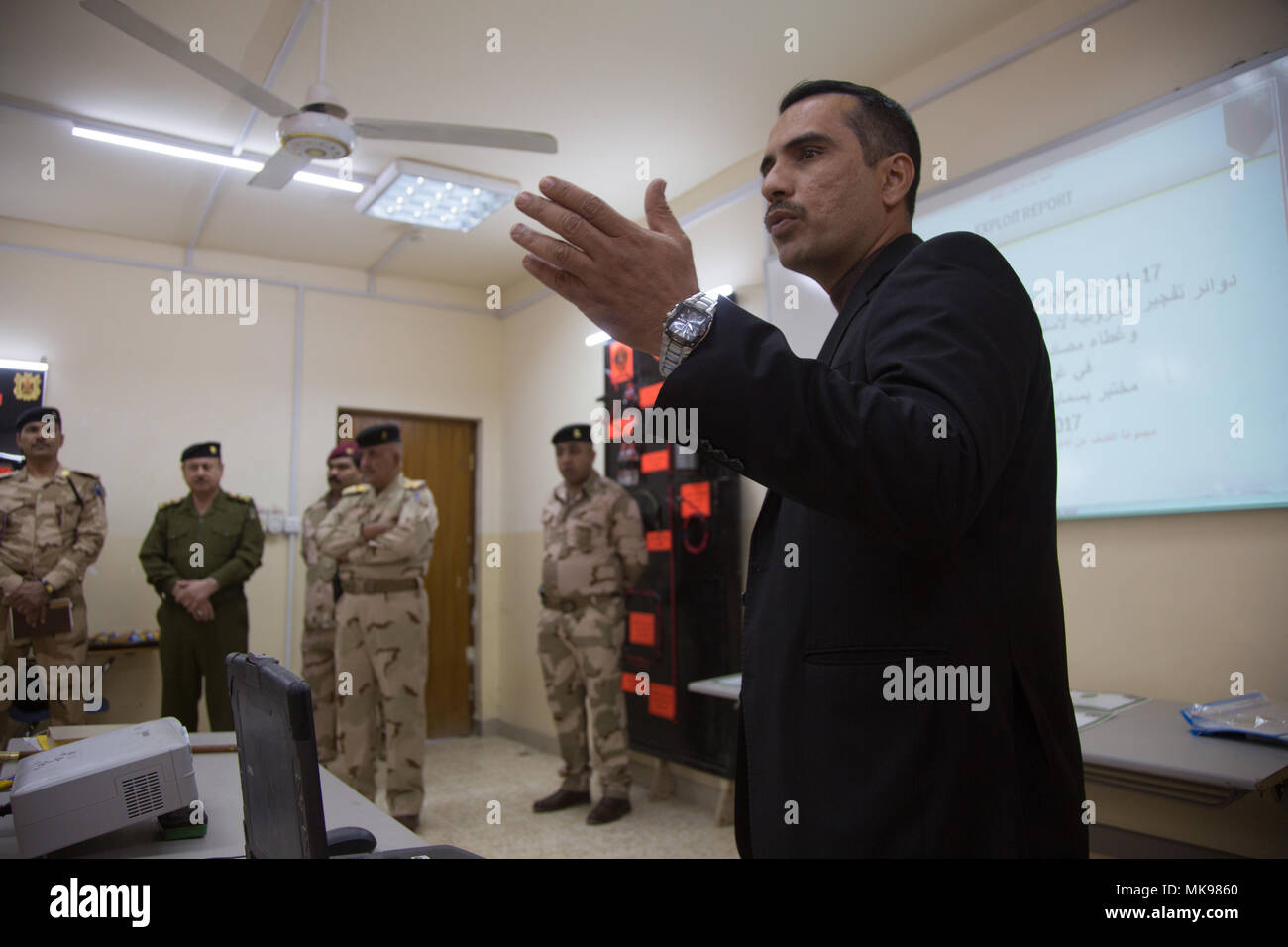 An Iraqi soldier gives a presentation during a counter improvised explosive device exploitation class graduation at the Besmaya Range Complex, Iraq, Nov. 29, 2017. This presentation is to show the class what he's learned throughout the several week course. The Besmaya Range Complex is one of four Combined Joint Task Force - Operation Inherent Resolve building partner capacity locations dedicated to training partner forces and enhancing their effectiveness on the battlefield. CJTF-OIR is the global Coalition to defeat ISIS in Iraq and Syria. (U.S. Army photo by Sgt. Mitchell Ryan) - Stock Image