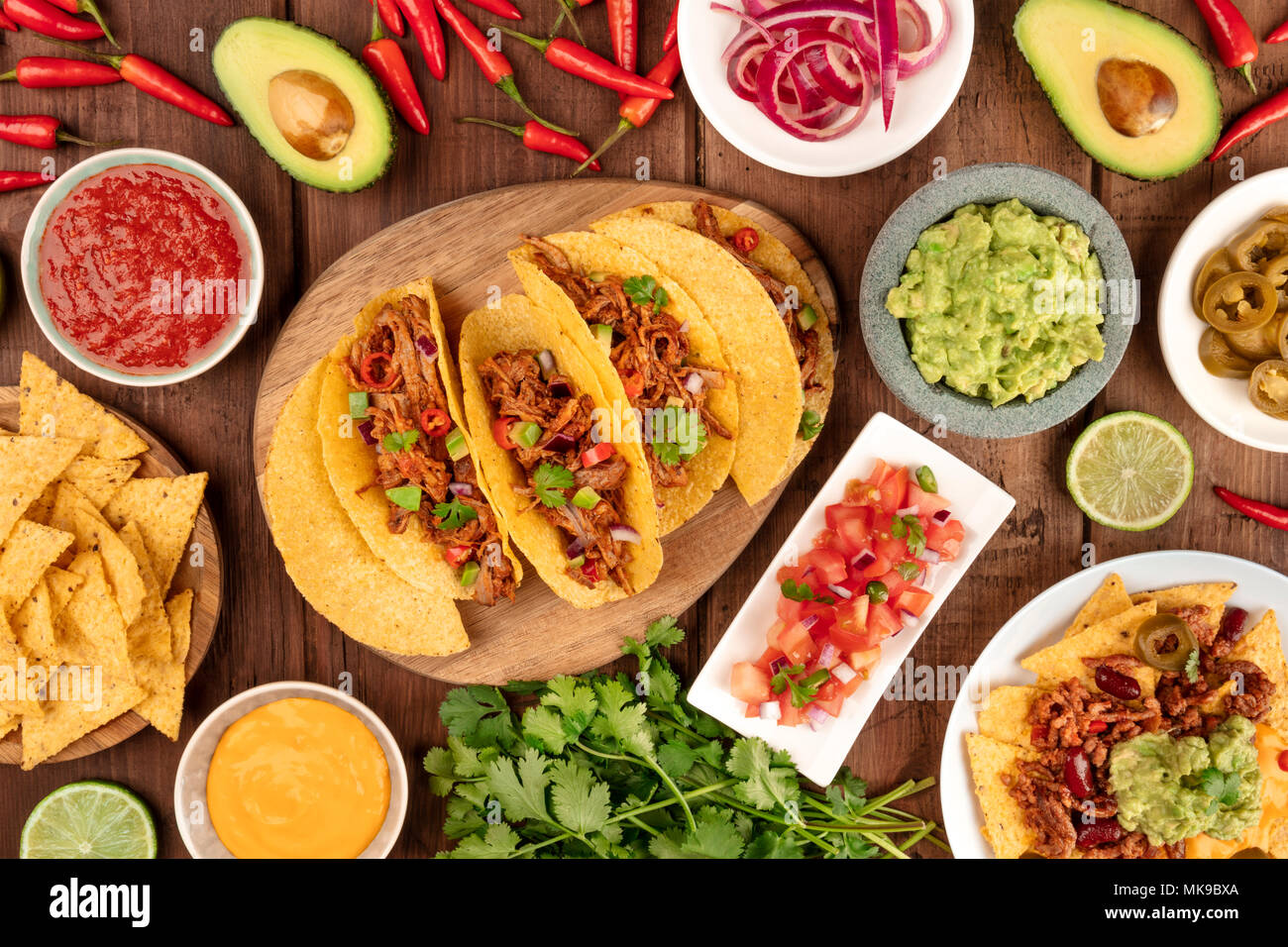 An overhead photo of an ssortment of many different Mexican tapas, including tacos, guacamole, pico de gallo, nachos and others - Stock Image