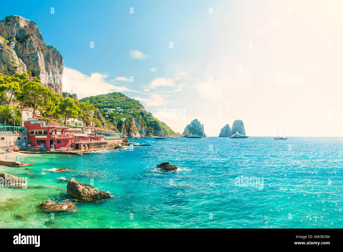 view of faraglioni rocks at sunset from Marina Piccola beach on summer day with turquoise blue waters and beachfront cafes, Capri, Italy Stock Photo