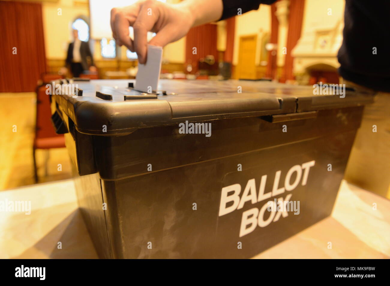 Person posting a vote into a ballot box during an election - Stock Image