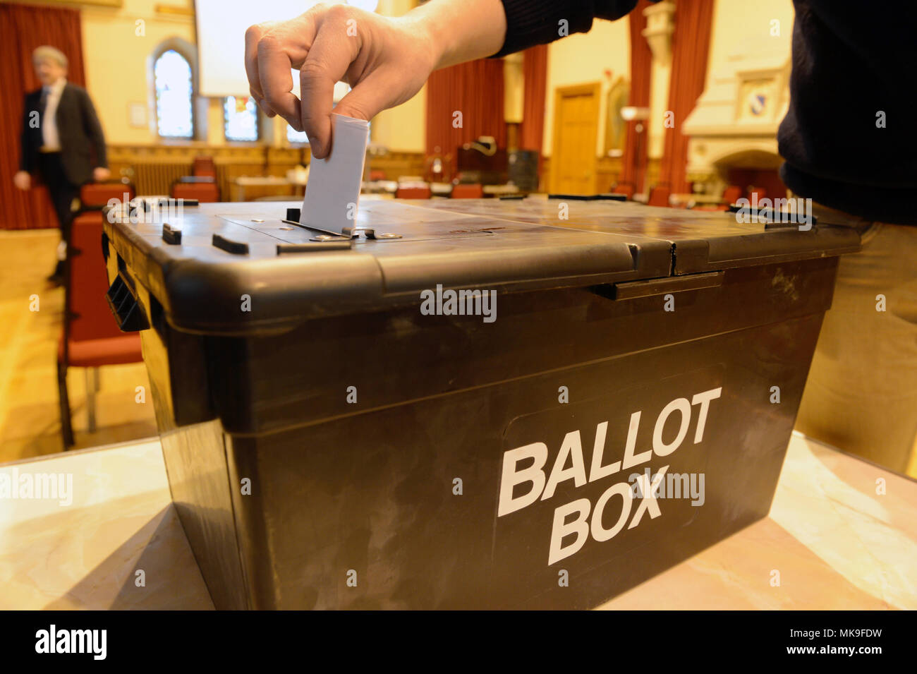 Person posting a vote into a ballot box during an election Stock Photo