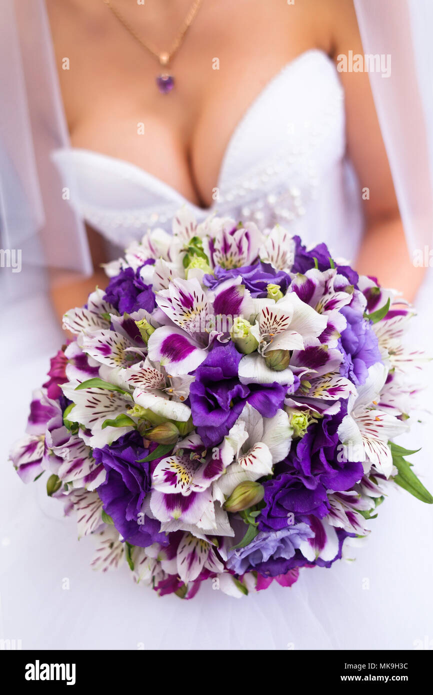 Bride in a white wedding dress holding purple bouquet beautiful bride in a white wedding dress holding purple bouquet beautiful bridal decollete dress mightylinksfo