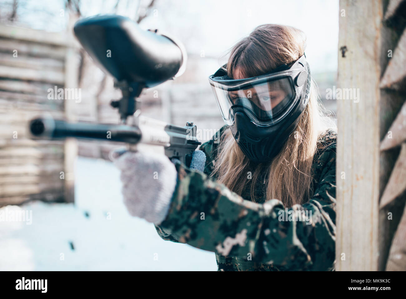 Female paintball player with marker gun in hands, winter forest battle. Extreme sport game, woman fights in protection mask and uniform Stock Photo