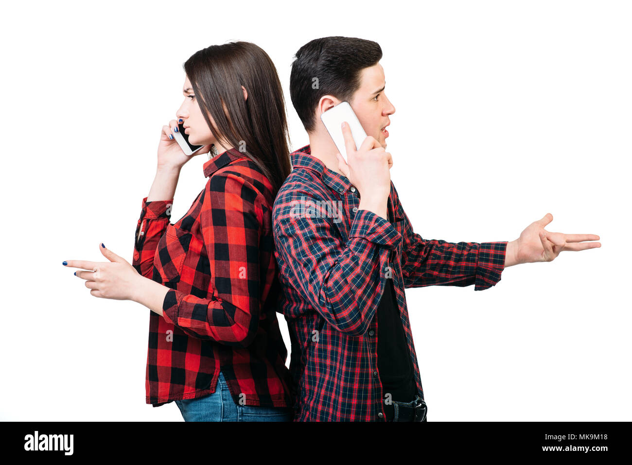 Smartphone addicted people. Couple standing back to back, talking by mobile phones, white background. Manipulation of consciousness concept - Stock Image