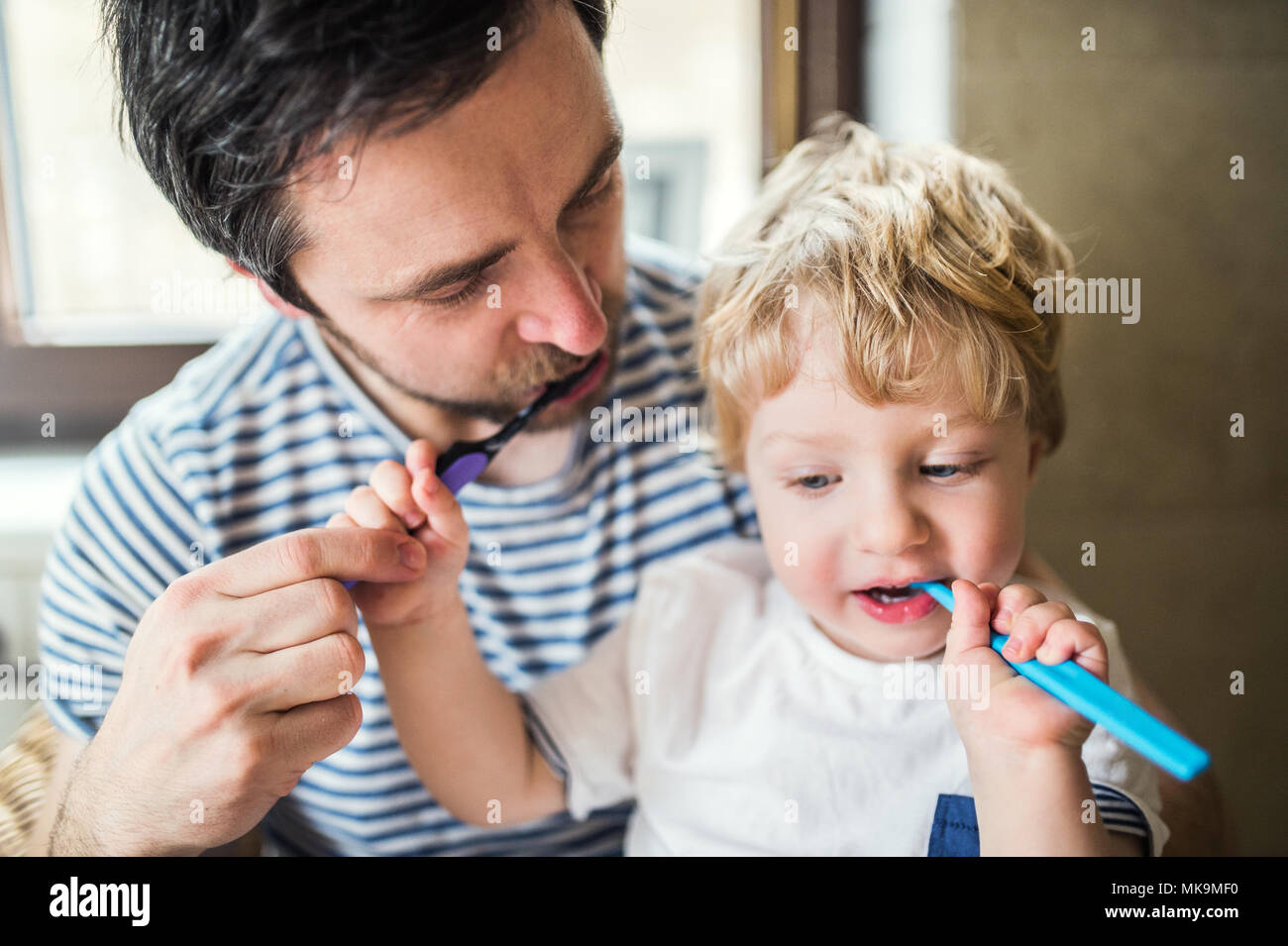 Father brushing his teeth with a toddler boy at home. Stock Photo