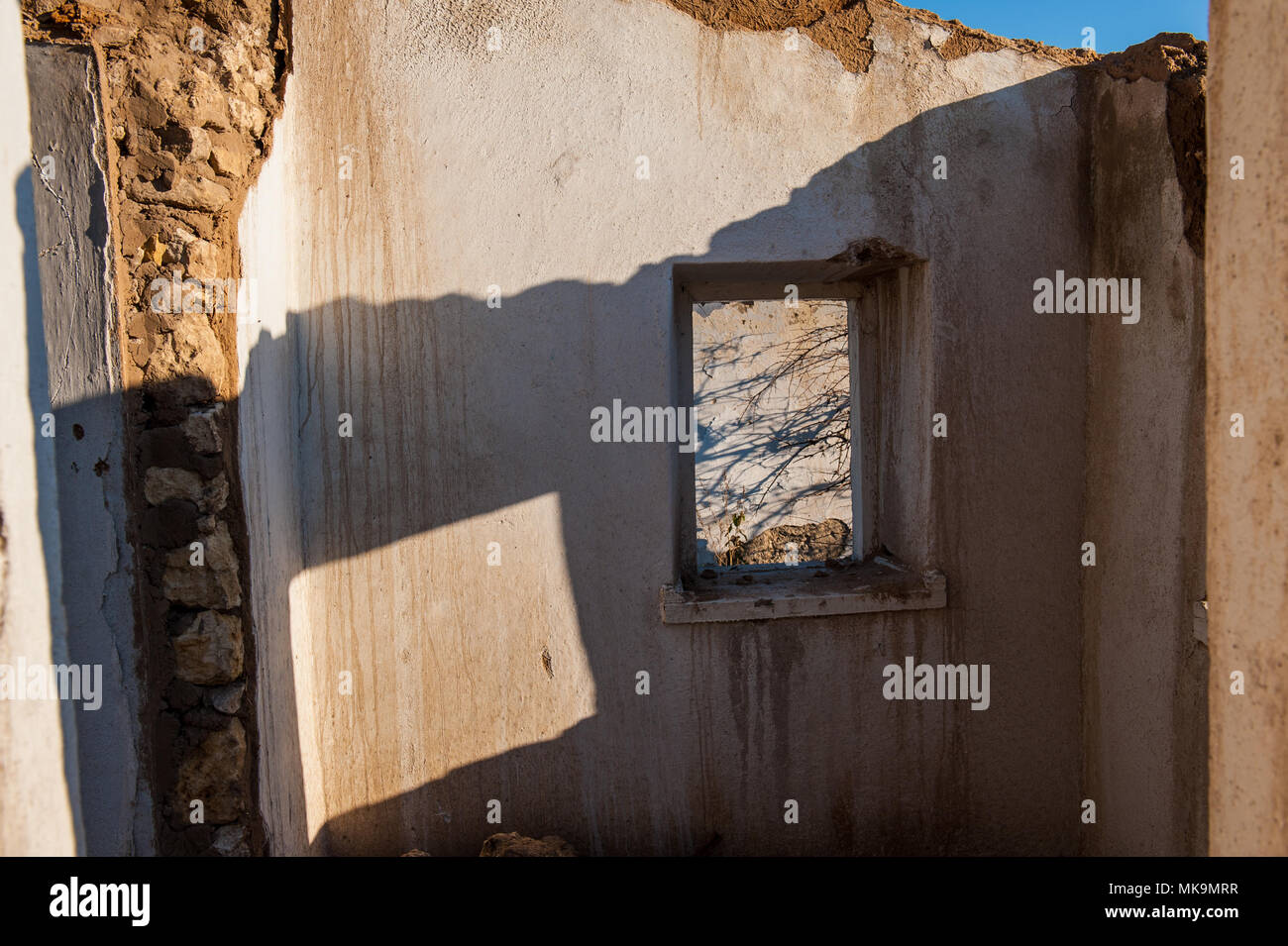 DESTROYED FORGED OLD HOUSE IN THE RURAL LOCATION. REMAINS OF WALLS AND WINDOWS. - Stock Image