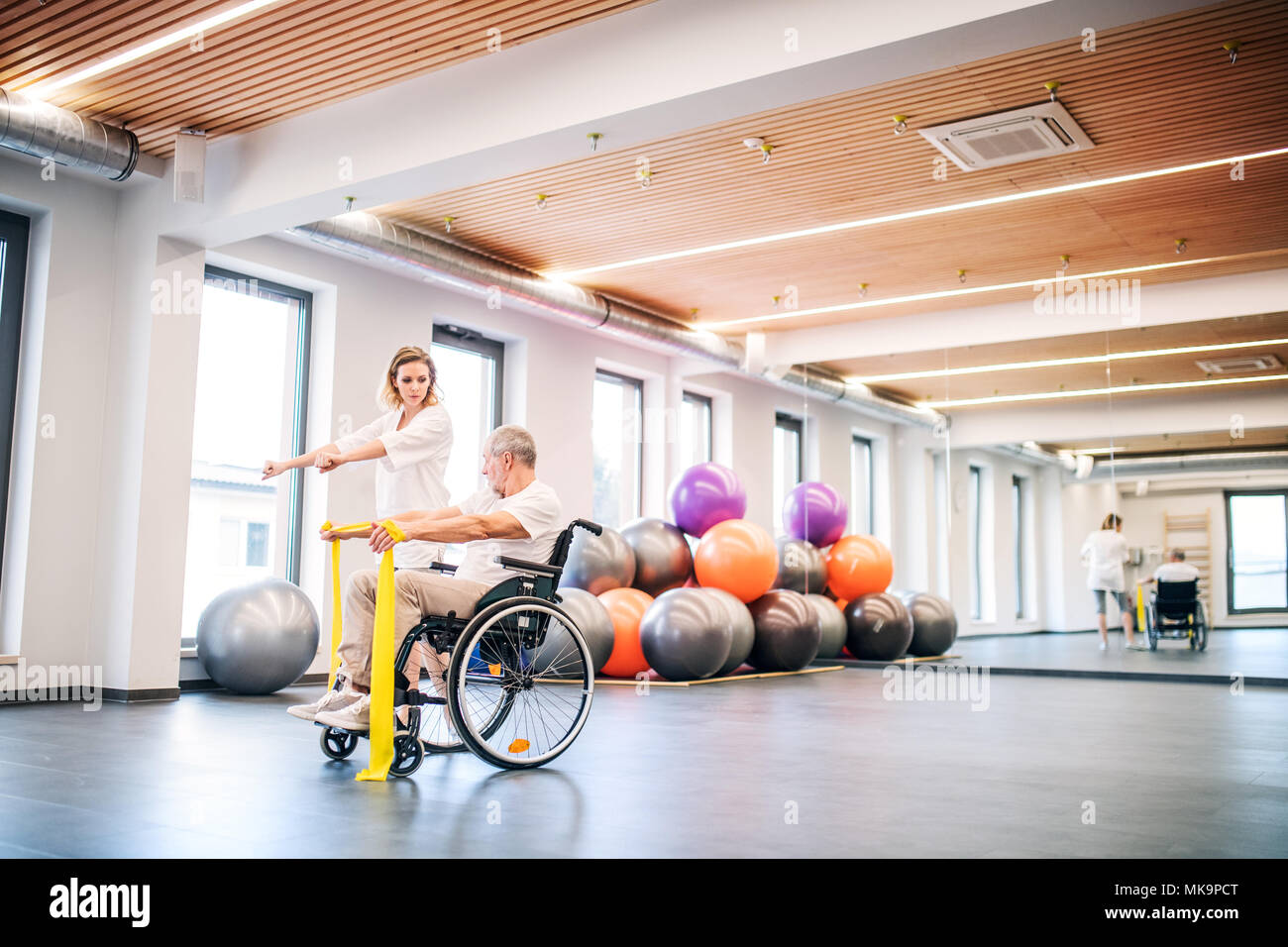 Young woman physiotherapist working with a senior man in wheelchair. - Stock Image