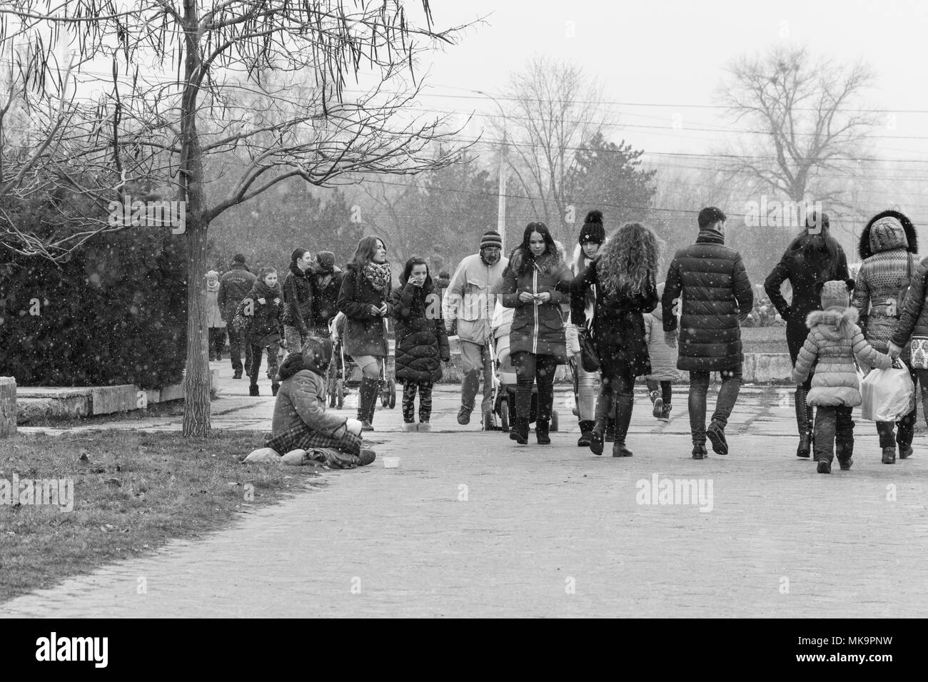 A group of people walking through a winter park, a reportage photo in black and white. - Stock Image