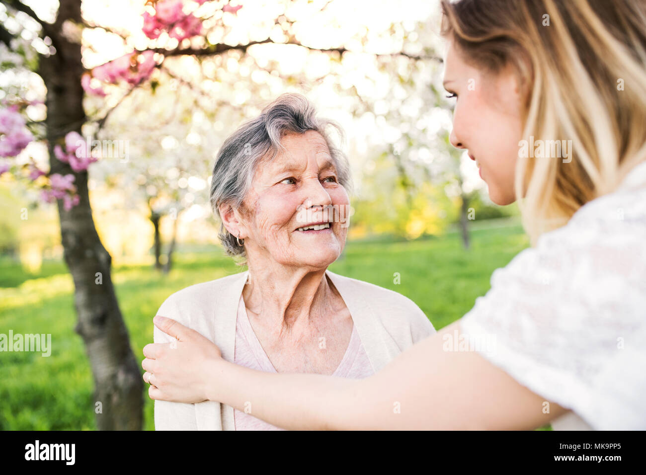 Elderly grandmother and granddaughter in spring nature. - Stock Image