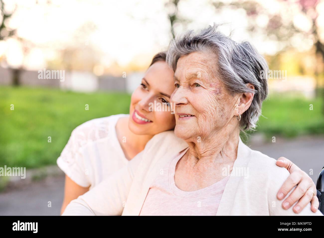 Elderly grandmother and granddaughter hugging in spring nature. - Stock Image
