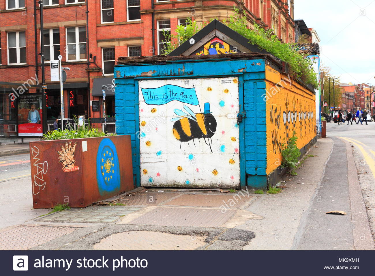 A painting of the Manchester Bee on a blue & yellow building with plants growing on the roof in Manchester City Centre England May 2018 - Stock Image