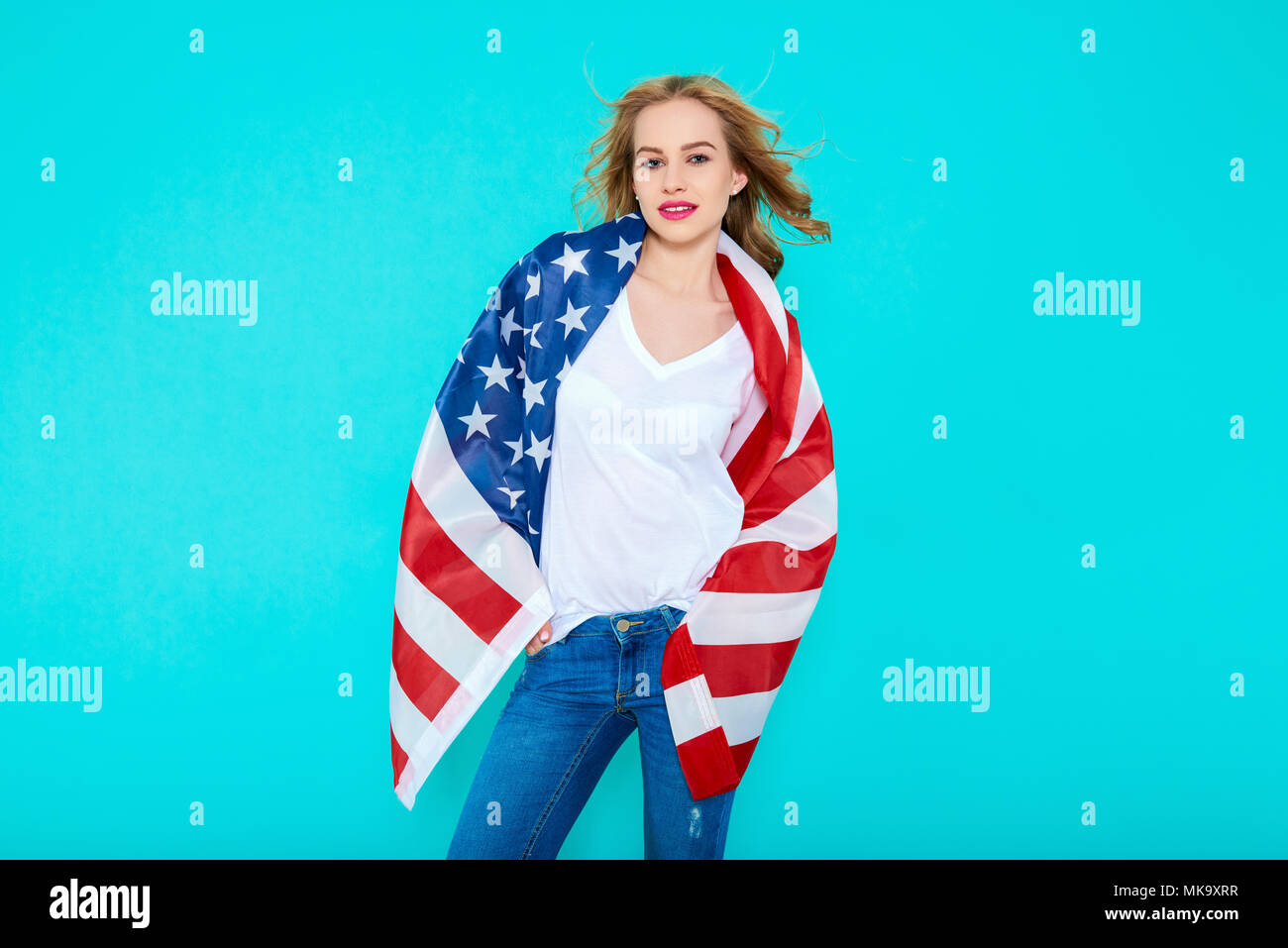 I love America. Happy young smiling woman in jeans and white Tshirt holding American flag and looking at camera while standing against pastel blue bac - Stock Image