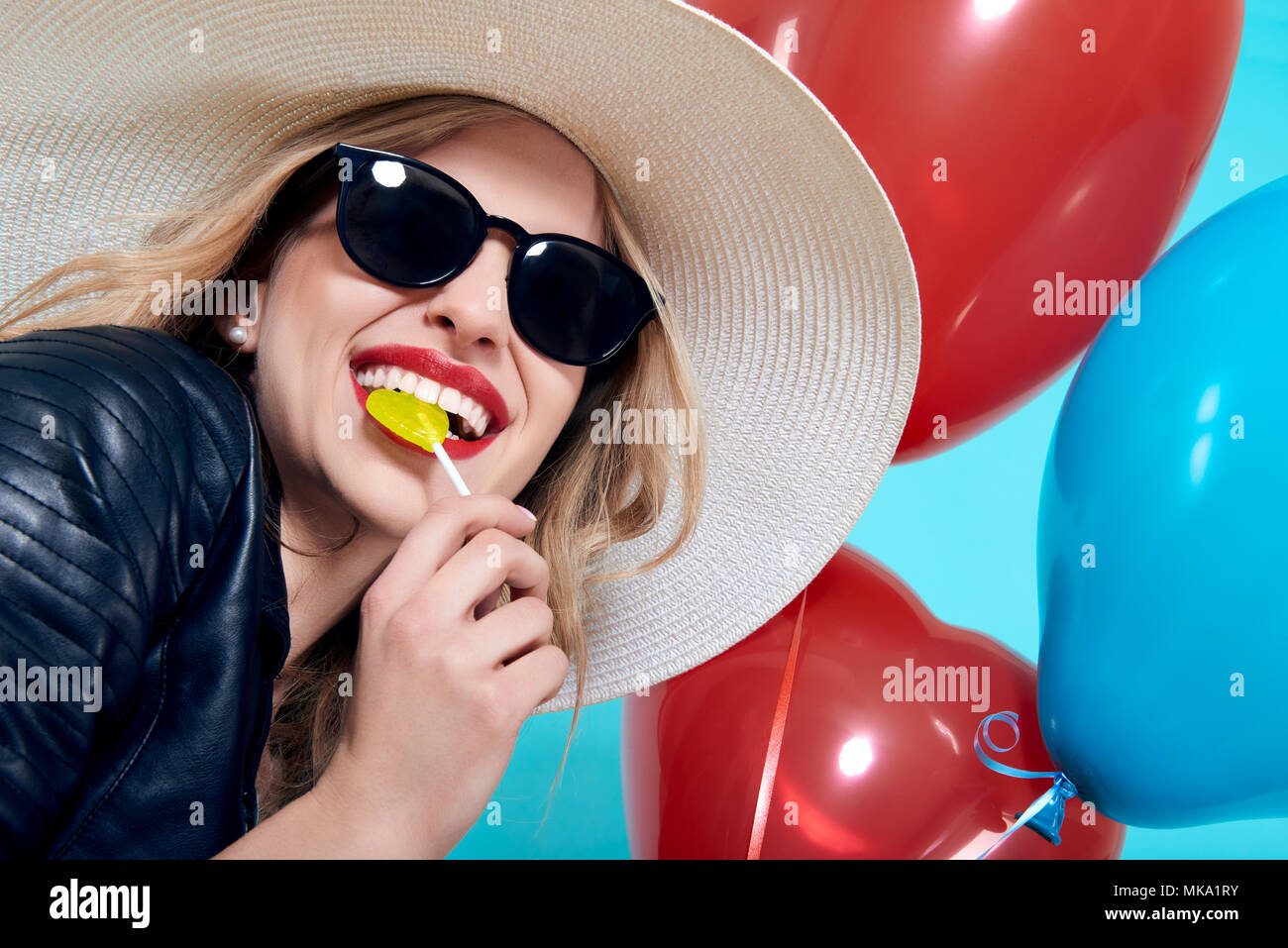 Beautiful rocker girl in leather jacket and sunglasses with heart shaped lolipop and heart shaped balloons. Attractive cool young woman fashion portra - Stock Image