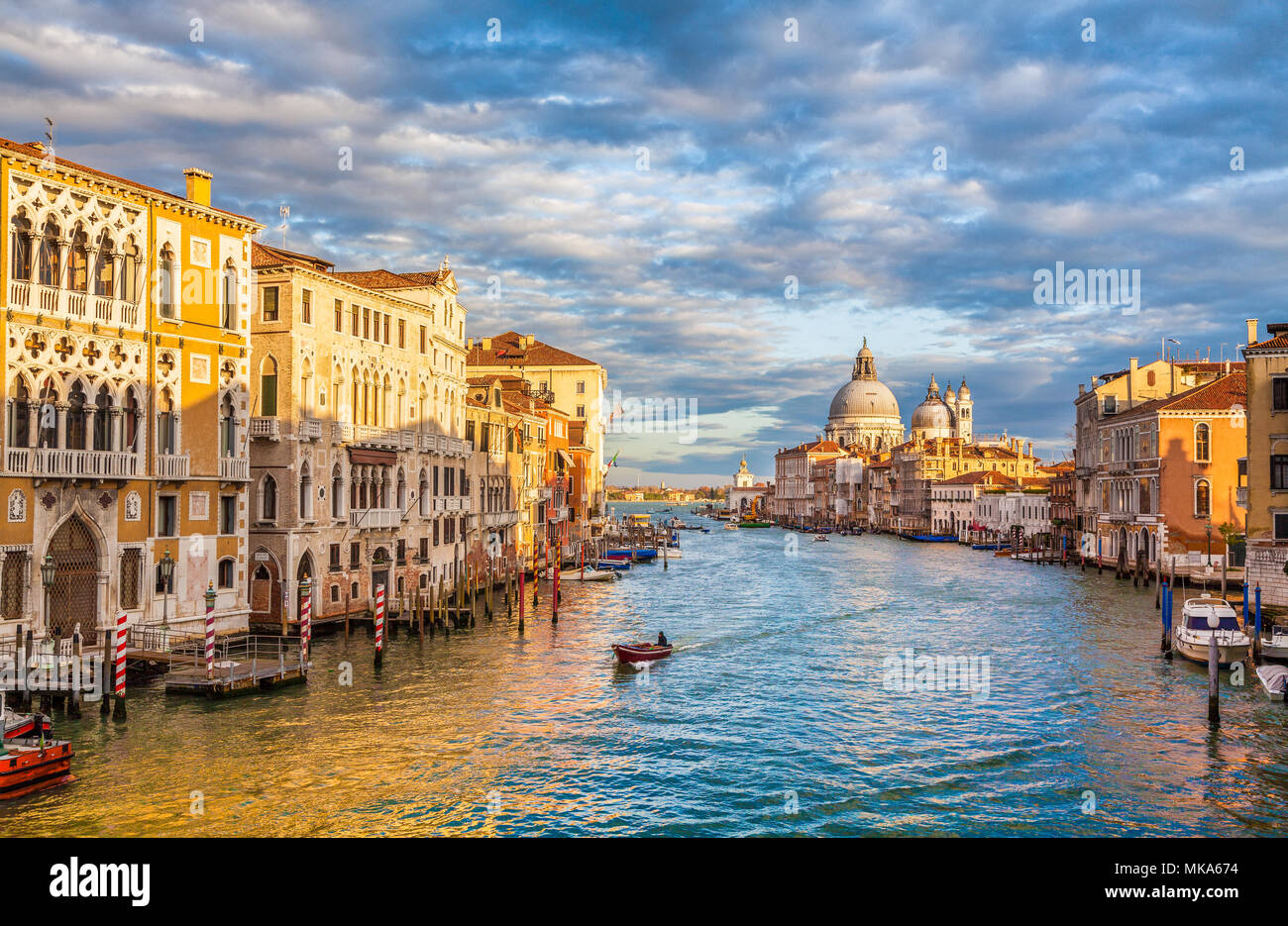 Classic panoramic view of famous Canal Grande with scenic Basilica di Santa Maria della Salute in beautiful golden evening light at sunset, Venice, It - Stock Image