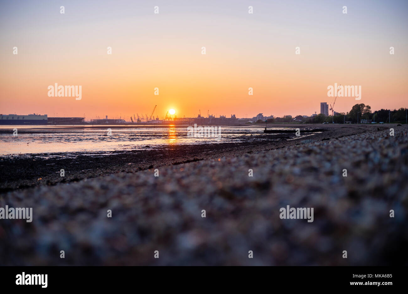 Sunset over Southampton Docks during low tide, view from Weston Shore, Hampshire, England, UK - Stock Image