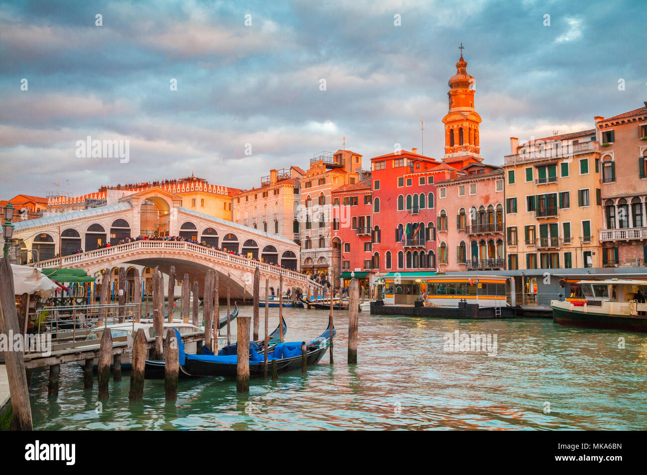 Classic panoramic view with traditional Gondolas on famous Canal Grande with famous Rialto Bridge in the background in beautiful golden evening light  - Stock Image