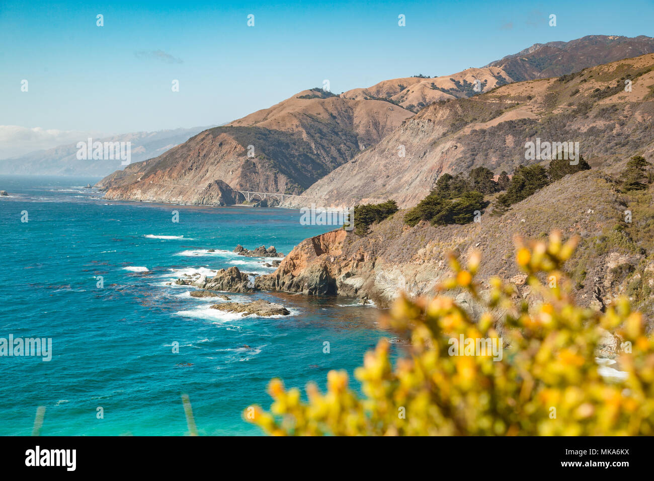 Scenic view of the rugged coastline of Big Sur with Santa Lucia Mountains and Big Creek Bridge along famous Highway 1 at sunset, California, USA - Stock Image