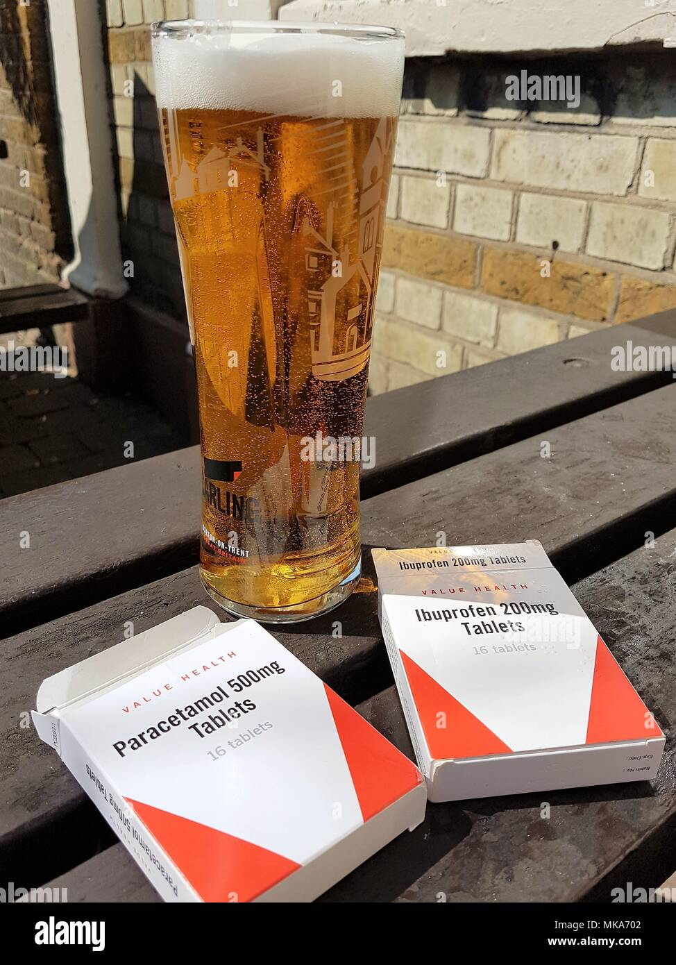 A pint of Carling lager and empty packets of Paracetamol and Ibuprofen on a wooden bench in a pub garden, hangover cure?. Stock Photo