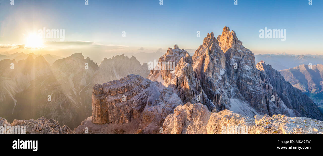 Beautiful view of famous Tre Cime di Lavaredo mountain summits in the Dolomites mountain range illuminated in beautful golden evening light at sunset  - Stock Image