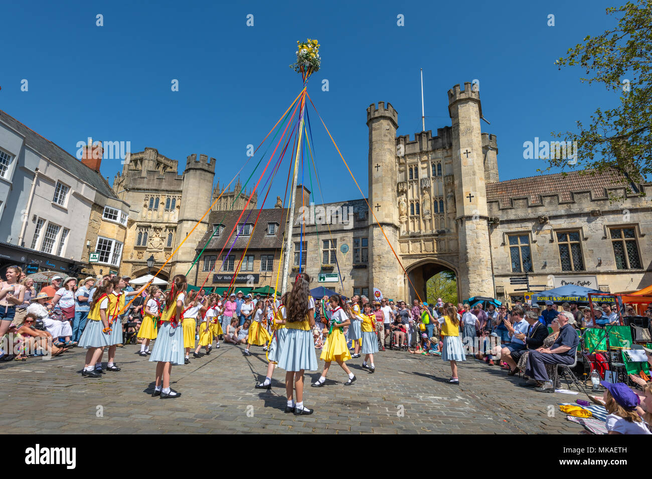 Wells, Somerset, UK. 7th May, 2018. UK Weather - On a beautiful sunny Bank Holiday Monday in Somerset, the pupils of St. Joseph and St. Theresa and Stowberry Park Primary Schools entertain a large crowd with Maypole Dancing to welcome the start of summer in Wells City Market Place. Credit: Terry Mathews/Alamy Live News - Stock Image