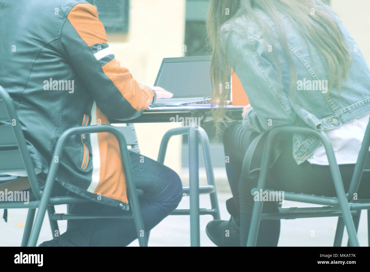Man and woman peers with a laptop with wifi connection sitting on a cafe. Teleworking concept and empty copy space for Editor s text. Stock Photo