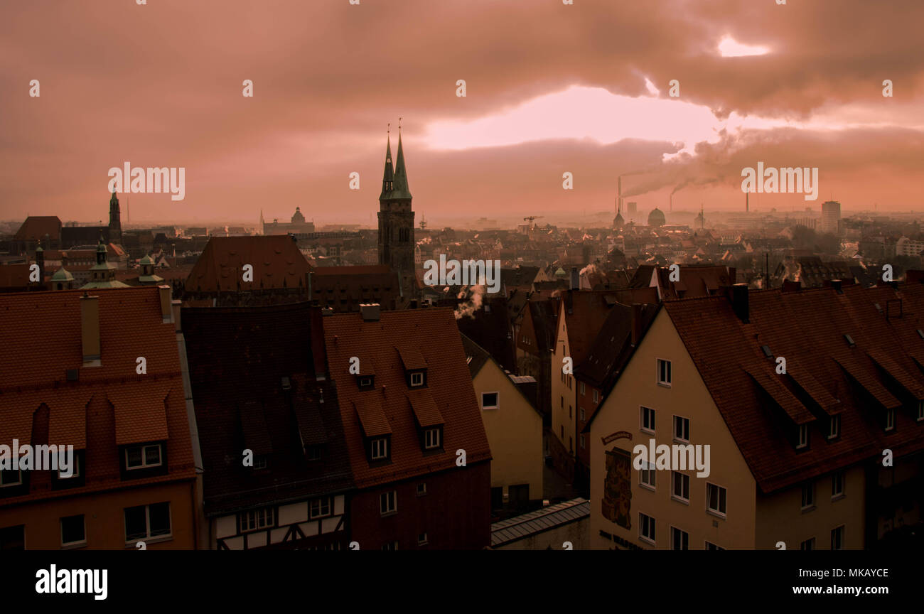 Nuremberg, Germany - pollution from fossil fuels above the skyline of the city at sunrise image with copy space - Stock Image
