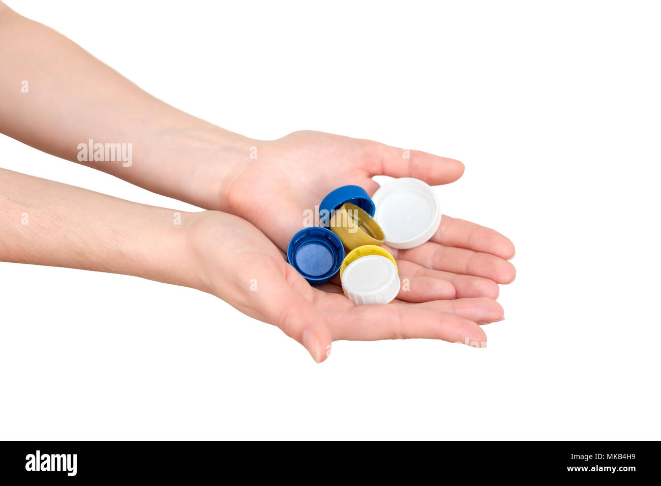 Female hand holding plastic bottle caps. Two hands with plastic lids. Recyclable waste. Recycling, reuse, garbage disposal, resources, environment and - Stock Image