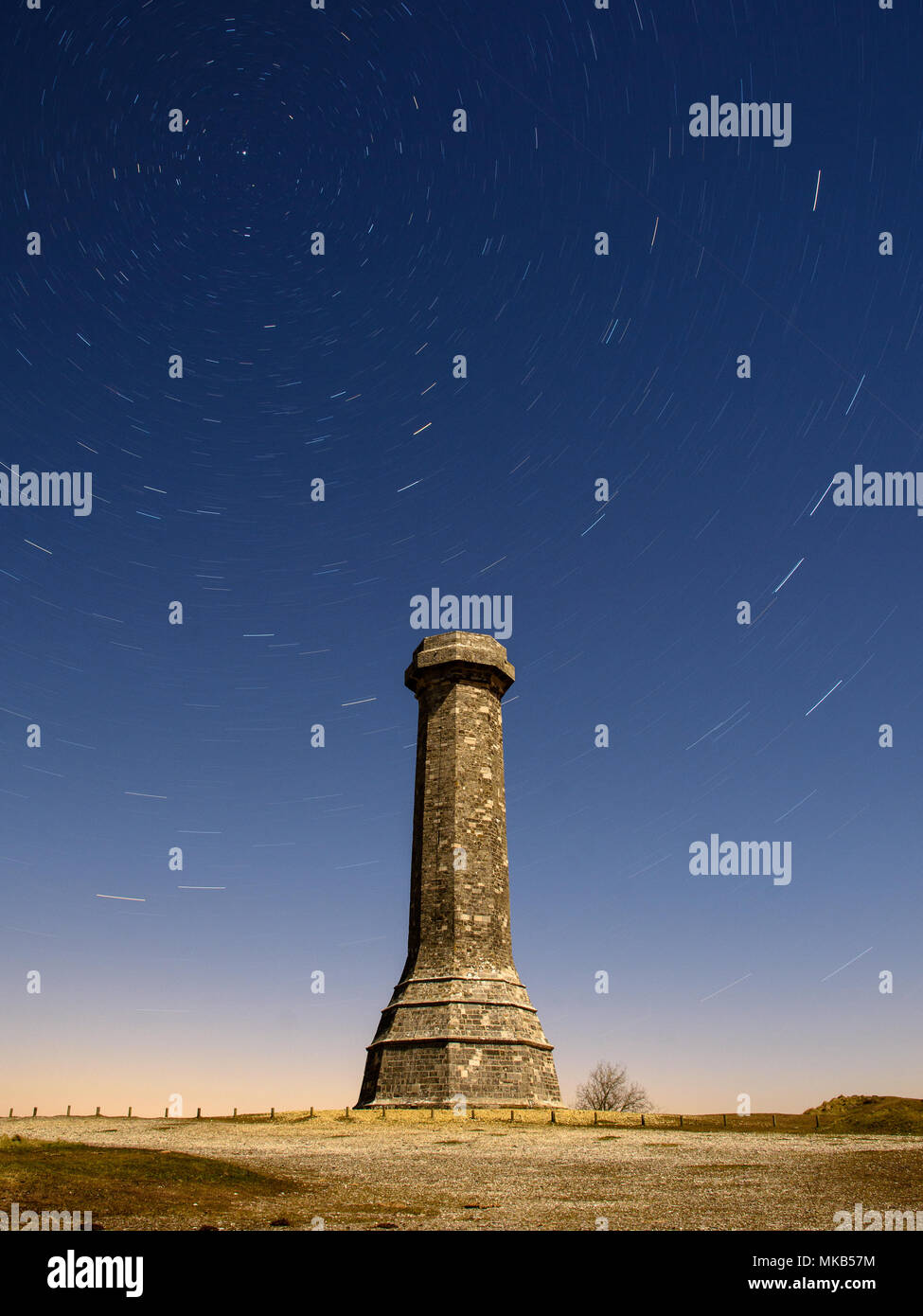 Stars leave trails in the night sky in a long exposure photograph of a moonlit Hardy Monument in the Dorset Downs. - Stock Image